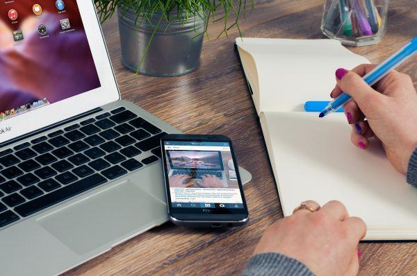 laptop, smartphone en notitieblock met vrouw die schrijft