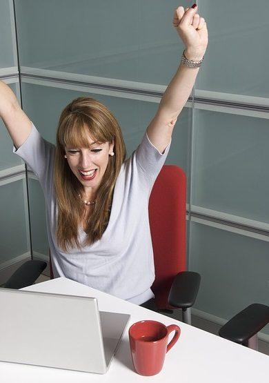 vrouw achter laptop handen juichend omhoog