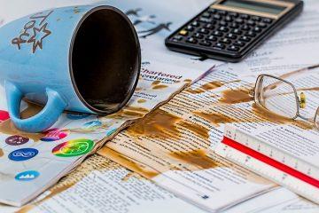 koffiemok met inhoud gevallen over papieren